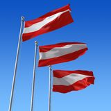 Three flags of Austria against blue sky. Royalty Free Stock Photos