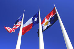 Three flags Dallas, Texas, America against blue sky Royalty Free Stock Photo