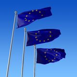 Three flags of Europe Union against blue sky. Royalty Free Stock Photo