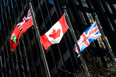 Three flags: Ontarian, Canadian, British. The Ontarian, Canadian, and British flags flying proudly in the bright sunlight in downtown Toronto Royalty Free Stock Photos