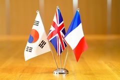 Flags of South Korea, UK and France. Three flags on the table. Flags of South Korea, United Kingdom and France. Flags of South Korea, France and UK on the table royalty free stock photo