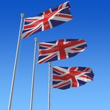 Three flags of UK against blue sky. Stock Photos