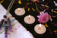 Three flames. Three teelights next to a hand towel with fresh flowers and petals Royalty Free Stock Photos