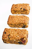 Three flapjack pieces in a row. Three pieces of fresh homemade cherry and raisin flapjack, in a row on a white table cloth with short depth of field Royalty Free Stock Photography