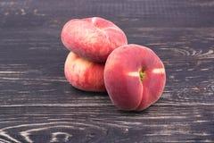 Three flat peaches Stock Photos