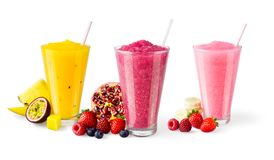 Three Flavors of Blended Fruit Smoothies on White Background. Three flavors of cold blended fruit smoothies, shakes, or cocktails in glasses with straws. The royalty free stock images