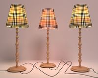 Three floor lamps on wooden legs on a light background Royalty Free Stock Photography