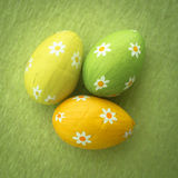 Three foil wrapped easter eggs on green surface Stock Image
