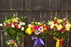 Three flower bouquets on a wooden background royalty free stock photos