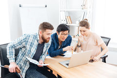 Three focused businesspeople working with laptop in office Stock Images