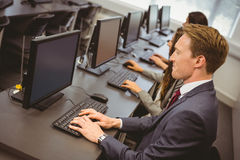 Three focused people working in computer room Stock Photo