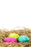 Three foil wrapped easter eggs nestled in straw nest Stock Images