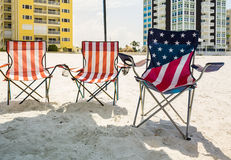 Three folding beach chairs under shade on beach. Three folding chairs on sandy beach in the design of US flag of stars and stripes Royalty Free Stock Photography