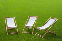 Three folding chairs in a green park. Three folding chairs on green grass in a park Stock Photo