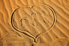 Three footprint and heart on sand Stock Photos