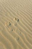 Three Footprints. On the wavy sand stock image