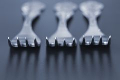 Three forks with shallow depth of field. Three forks on a gray background close-up with shallow depth of field, casting shadows Royalty Free Stock Images