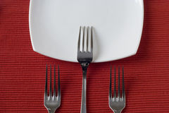 Three forks and porcelain plate Royalty Free Stock Photo