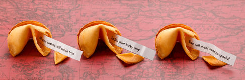 Three Fortune Cookies. Three open fortune cookies on a world map with the sayings All your wishes will come true, Today is your lucky day and You will meet Royalty Free Stock Photos
