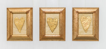 Three framed gold hearts, white background. Close up. Stock Images