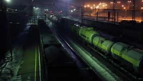 Three freight trains move on railway at winter night. Three long freight trains move on railway at winter night stock video