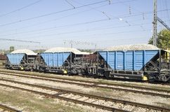 Three freight wagons with gravel on the siding. On station Royalty Free Stock Images