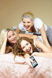 Three freinds watching TV. Three happy pretty girls on the bed at home watching TV, fighting for the  panel and laughing Royalty Free Stock Photos