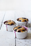 Three french clafoutis with blueberries and cherries on ceramic ramekins on rustic vintage background Royalty Free Stock Photos