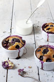 Three french clafoutis with blueberries and cherries on ceramic ramekins on rustic white vintage background with milk glass Royalty Free Stock Image