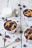 Three french clafoutis with blueberries and cherries on ceramic ramekins on rustic white vintage background with milk glass Stock Photo