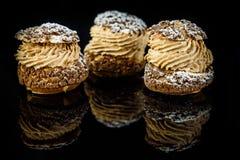 Three french dessert shoo served on black background. Three french dessert shoo with caramel cream filling served on black mirror background with reflection stock image