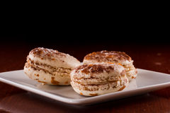 French macaroons. Three french macaroons served on a plate with a dark background Royalty Free Stock Image