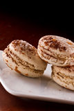 French macaroons. Three french macaroons served on a plate with a dark background Royalty Free Stock Photography
