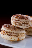 French macaroons. Three french macaroons served on a plate with a dark background Stock Images