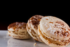 French macaroons. Three french macaroons served on a plate with a dark background Royalty Free Stock Photos