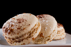 French macaroons. Three french macaroons served on a plate with a dark background Stock Photography