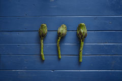 Three fresh artichokes on blue wooden table royalty free stock image