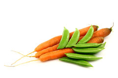Three fresh carrots and some sugar snaps. Isolated on white Royalty Free Stock Photo
