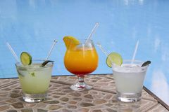 Three fresh drinks near the pool Royalty Free Stock Photos