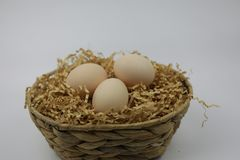 Three Fresh Eggs in  bamboo basket. Of straw isolated on white backgrond Royalty Free Stock Image
