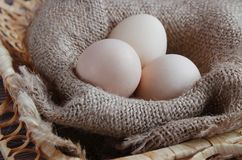 Three fresh eggs lie on a beige napkin in a basket. royalty free stock image