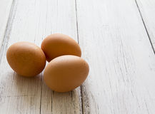 Three fresh eggs on a wood background Stock Images