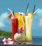 Three fresh juices. And coconut on the beach on the table royalty free stock photo