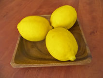 Three fresh lemons on a wooden plate Royalty Free Stock Photography