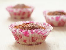 Three fresh muffins upon wooden table. Homemade pastry. Horizontal. Selective focus on the front Stock Image