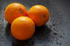 Three fresh oranges. On black background stock images