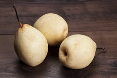 Three fresh pears on wooden table Stock Photo