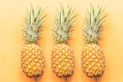 Three fresh pineapples lying on orange background. Top view. Flat lay concept. Place for text royalty free stock photos