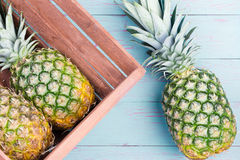 Three fresh pineapples, two in a wooden crate Stock Image