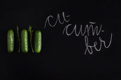 Three fresh raw cucumbers. Isolated on black background Stock Images